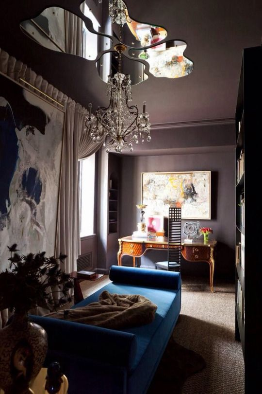a room with rug flooring, blue sofa, plants, wooden antique cabinet, large painting, curtain, glass application on the ceiling, chandelier
