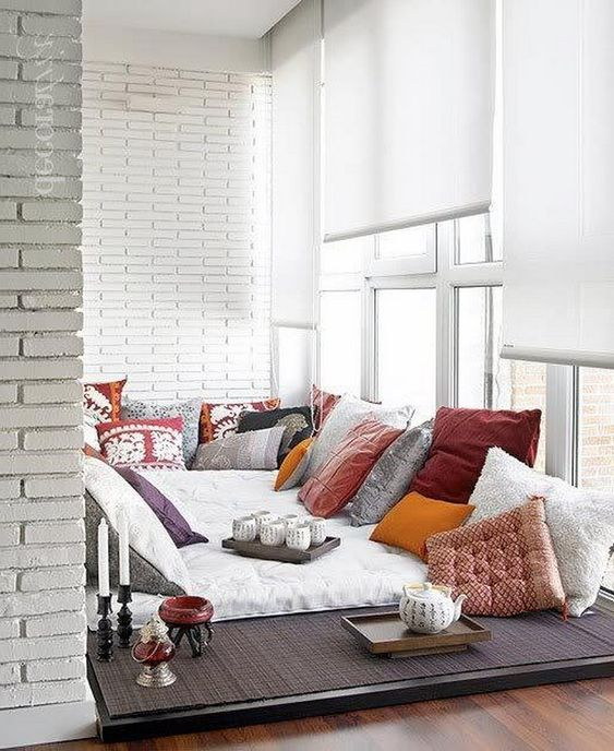 a room with white cushions with so many pillows, board for tea