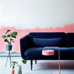 A Room With White Painted Wall But With Pink Paint On The Below, Dark Royal Blue Sofa, Pink Lamp, Plants