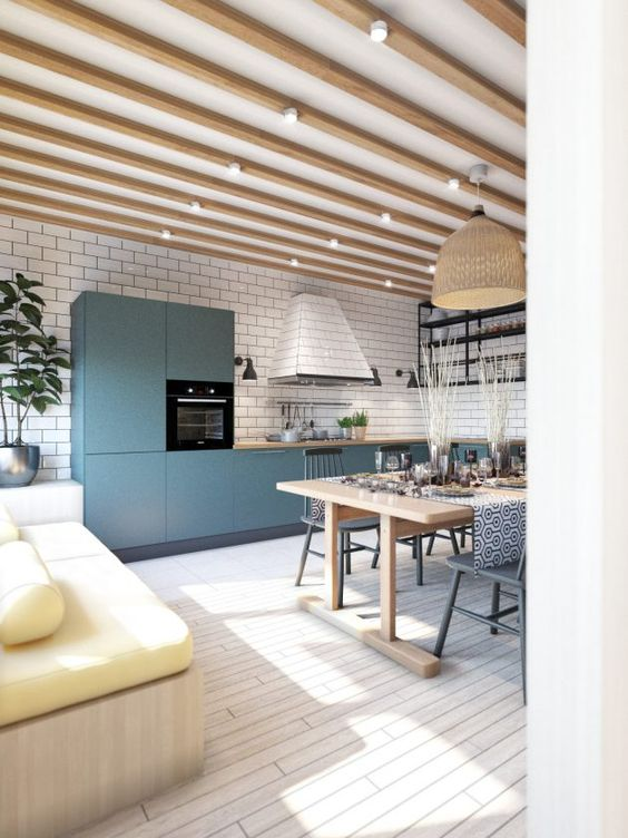 a room with wooden floor, wooden sofa, wooden table dining set, wooden cabinet in the kitchen, white tiles on kitchen wall