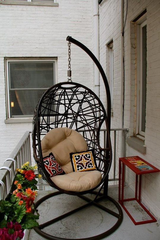 a small balcony with white floor, white open brick wall, flowers, table, a black swinging chair
