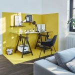 A Study Area With Dark Wooden Floor, White Wall, Yellow Painted Area, Glass Study Table, Black Chair, Grey Sofa