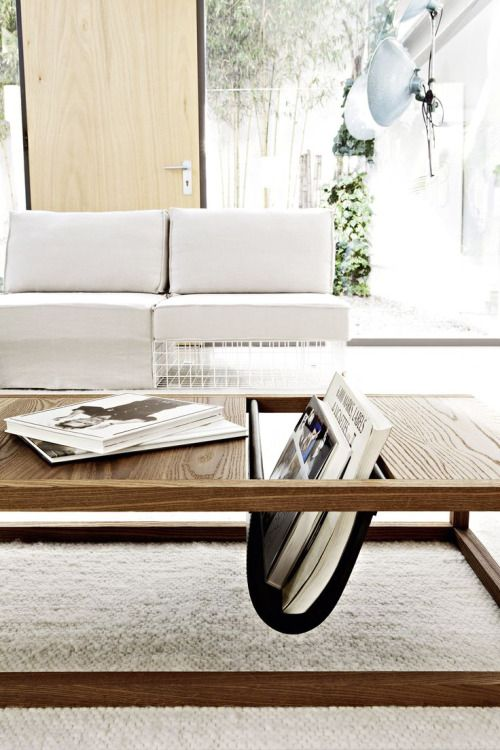 a wooden coffee table with metal or leather pocket in the middle for books