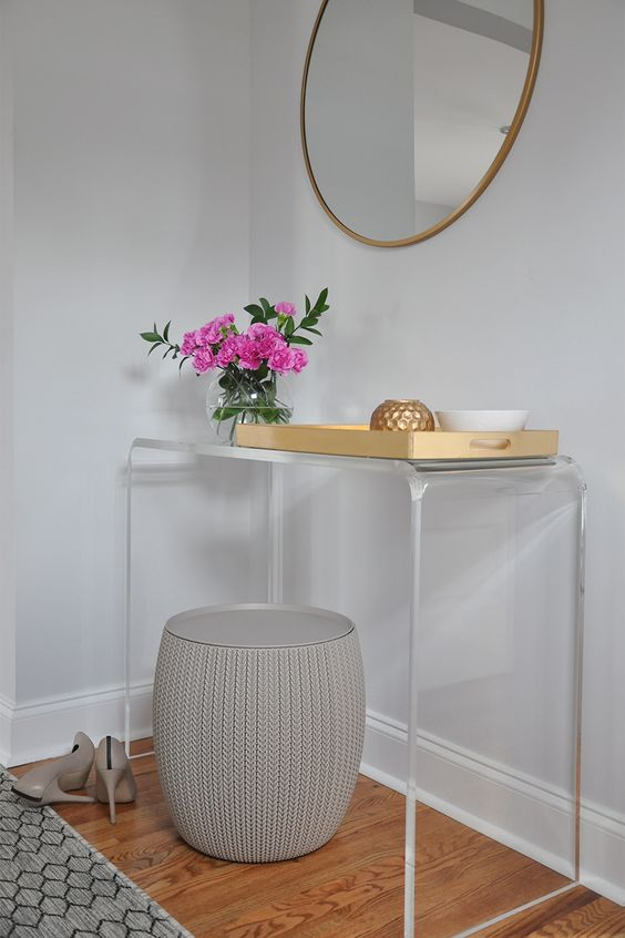 acrylic console table, wooden floor, golden framed mirror, grey stool