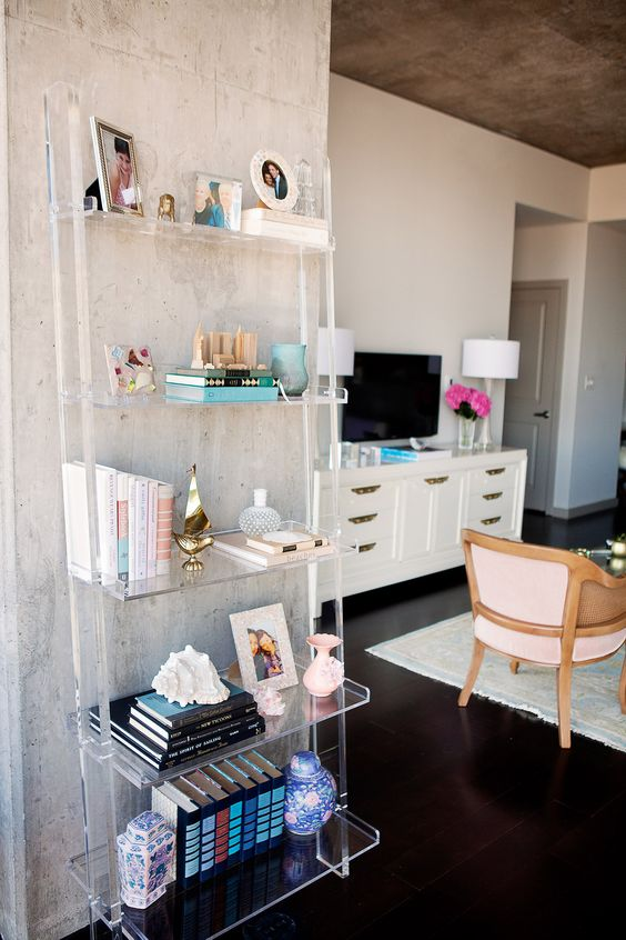 acrylic shelves, wooden floor, white cabinet, chairs, books, white table lamp, white wall
