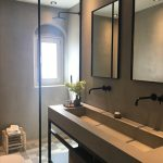 Bahtroom With Beige Floor, Concrete Sink Vanity With Rectangular Shape Dented For The Sink, Concrete Wall, Mirror, Black Faucet