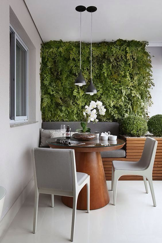 balcony, dining area, white floor, white wall, plants on the wall, wooden bench with grey cushions, built in pot