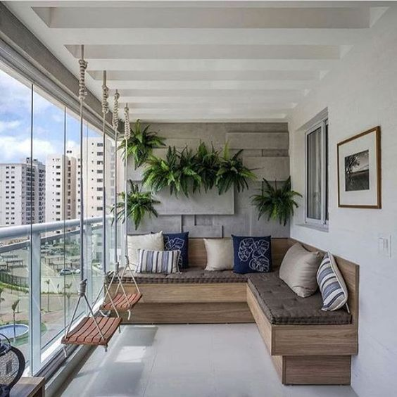 balcony with white floor, grey wall, corner wooden bench with grey cushion, swings, plants on the wall