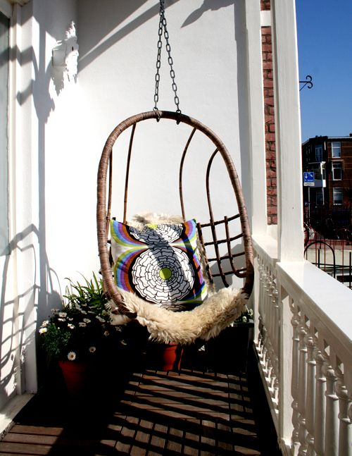 balcony with wooden floor, white posts and gences, white wall, plants flowers, swing hang from the ceiling