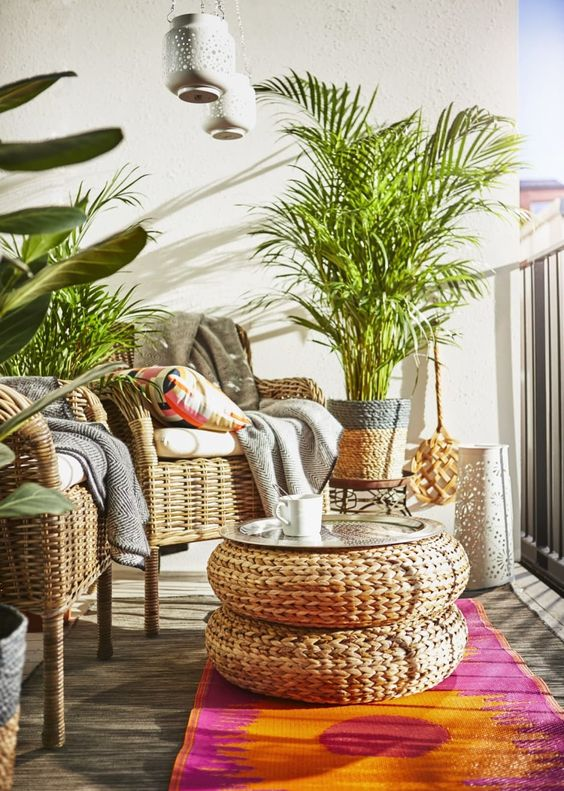 balcony, wooden gloor, colorful rug, rattan woven coffee table, rattan woven chairs, plants with rattan pot