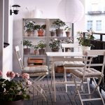 Balconywith Wooden Floor, Wooden Dining Set With Cushion On Chairs, Wooden Shelves For Plants, Sconces, Paper Pendant