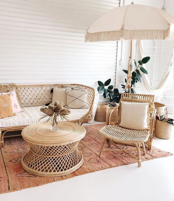bamboo and rattan material in sofa with white cuhion, chair, round coffee table, rug, white big umbrella