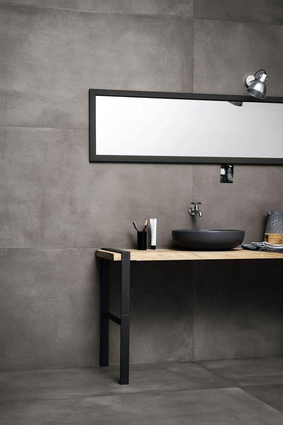 bathroom vanity with grey floor, grey wall, wooden vanity with metal legs, grey sink, long rectangular mirror, silver sconce