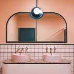 Bathroom Vanity With Pink Square Tiles Backsplash Till The Bottom, Peach Wall, Mirror, Lamp, Pink Sink, Pink Shelves With Pink Brown Marble Top