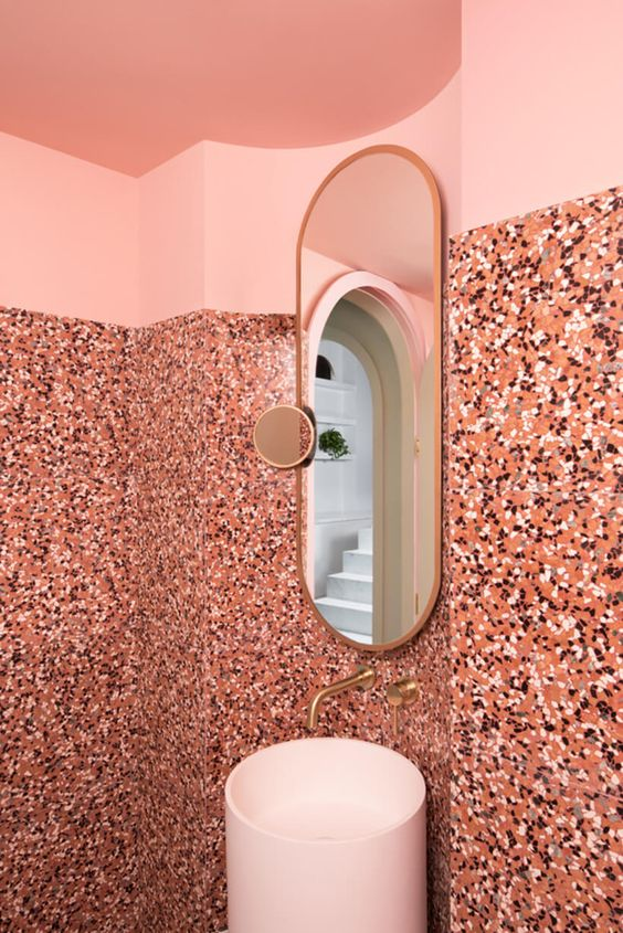 bathroom vanity with pink wall on top, pink terrazzo until almost ceiling, long mirror, white sink with golden faucet
