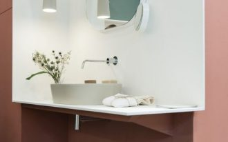bathroom vanity with white wall and vanity top, white sink, round mirror, pink wall outside the vanity area