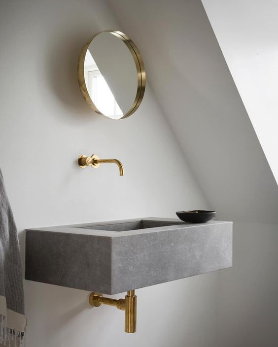 bathroom vanity with white wall, grey sink with golden faucet, golden frame small mirro