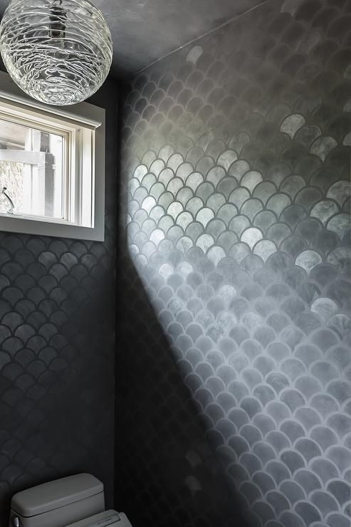 bathroom with black fish scales ceramic covering the wall, white toilet, window, modern pendant