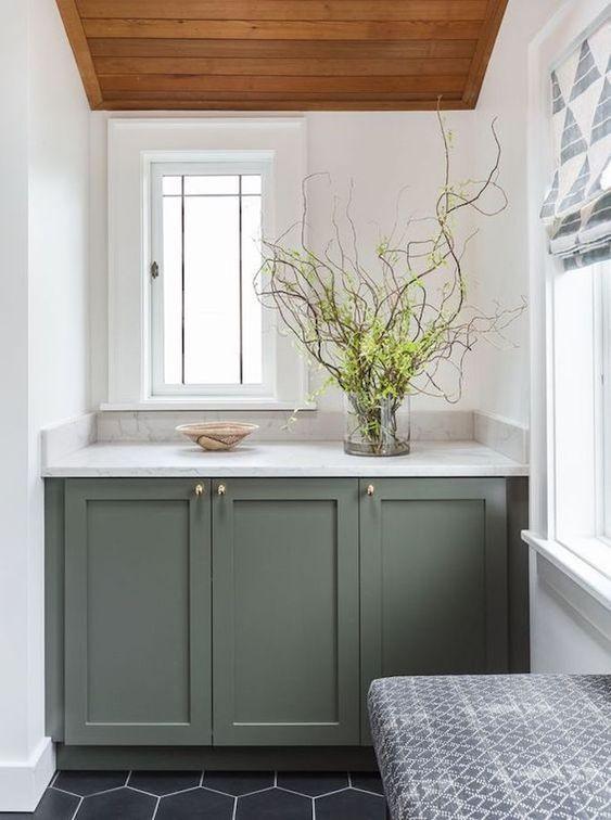 bathroom with black hexagon floor tiles, white walls, windows, geren sage cabinet with marble top