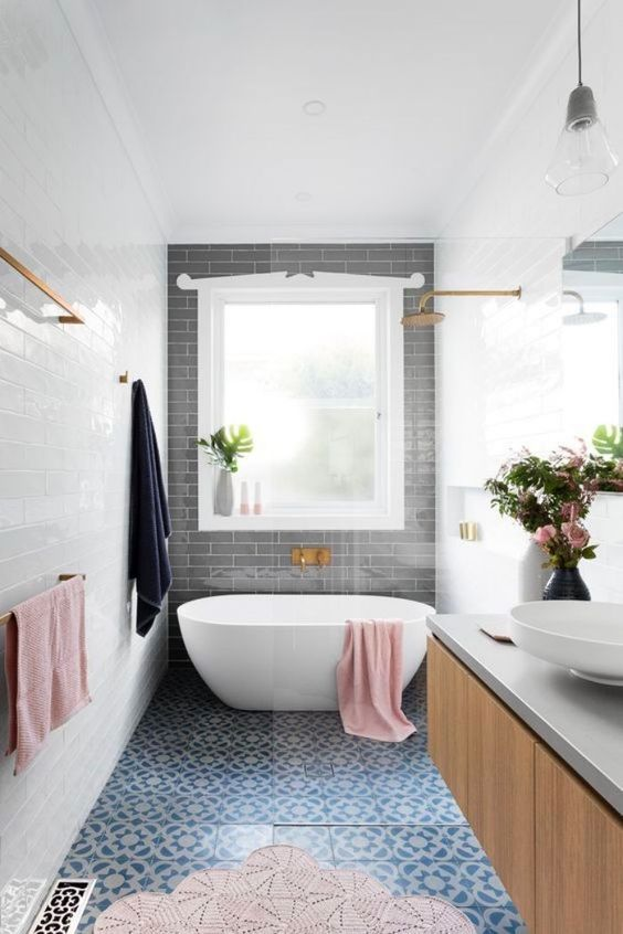 bathroom with blue tiles on floor, white tiles on wall, grey tiles accent wall, white framed window, white tub, wooden cabinet with grey op