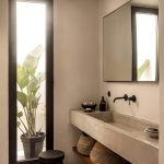 Bathroom With Brown Concrete Floor, Wall, Sink Vanity, Wooden Shelf Under, Mirror, Tall Window