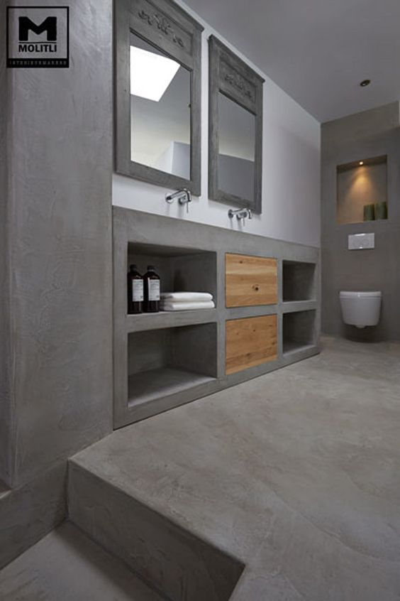 bathroom with concrete floor, concrete walls, concrete vanity and sink with shelves with wooden doors, grey mirror, white toilet
