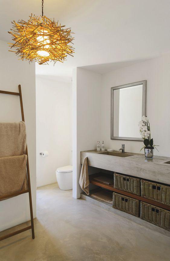 bathroom with concrete floor, white walls, concrete sink vanity, open shelves under, baskets, wooden rack, golden chandelier