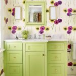 Bathroom With Flowery Wallpaper, Lime Colored Cabinet, White Tiles Floor, White Toilet, White Sconces, White Marble Top With Sink, Lime Framed Wall Mirror