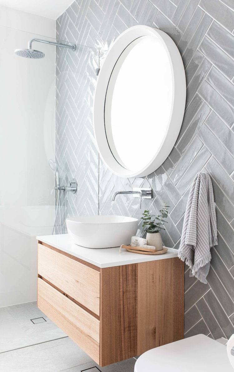 bathroom with grey floor, grey doble herringbone pattern on the wall, white frame round mirror, wooden floating cabinet with white top and white sink