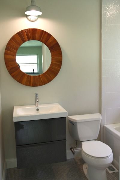 bathroom with grey floor, grey floating cabinet vanity with white sink top, round wooden mirror, white toilet