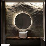 Bathroom With Grey Floor, Wooden Vanity White Sink, Round Mirror, Lamp Behid, Textured Wall, White Toilet