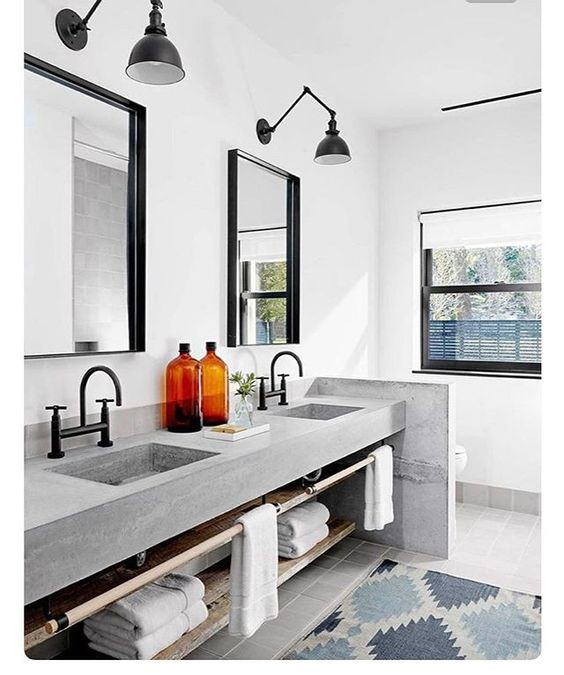 bathroom with grey square floor tiles, grey concrete sink vanity with black faucets, white wall, black framed mirror, black sconces, rug