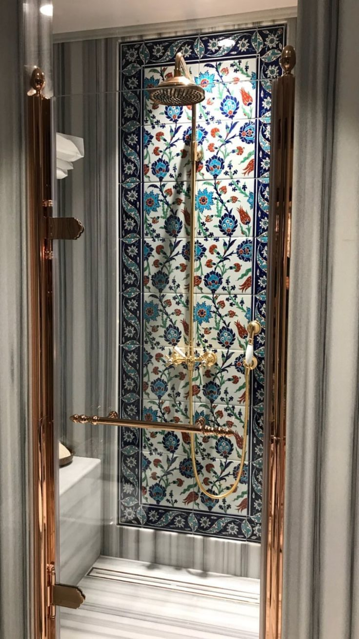 bathroom with grey stripes tiles on shower, glass window, blue pattern accent walls in shower, golden shower