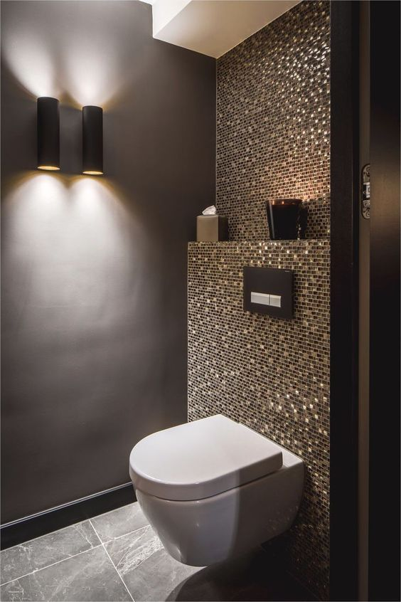 bathroom with grey wall, grey floor tiles, glowing tiles on the back of the white toilet, sconce