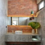 Bathroom With Grey Wall, Orange Bricks Accent Wall, Grey Bathroom Table With White Sink, Black Patterned Tiles