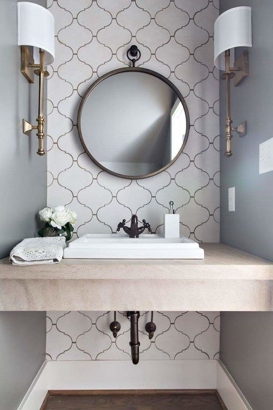 bathroom with light grey wall, brown wooden floor, white patterned accent wall, white sconce, white marble top with white sink dark brown faucet, round mirror
