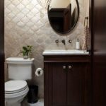 Bathroom With Marble Floor, White Toilet, Wooden Cabinet With White Marble Vanity, Round Mirror, Sconce, Pearl Colored Arabesque Tiles