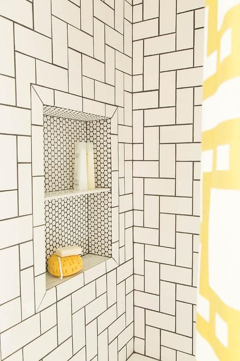bathroom with subway tiles on herringbone pattern on the wall with square depth on hexagon tiles
