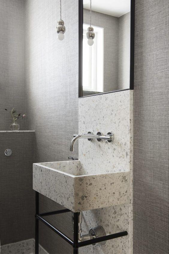 bathroom with terrazzo floor, grey wall, terrazzo sink and wall, mirror