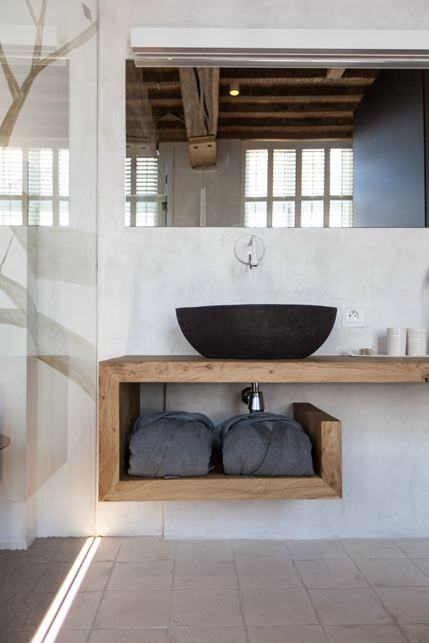 bathroom with tiles, glass partition, wooden floating vanity with unique shape, mirror, white wall, black sink