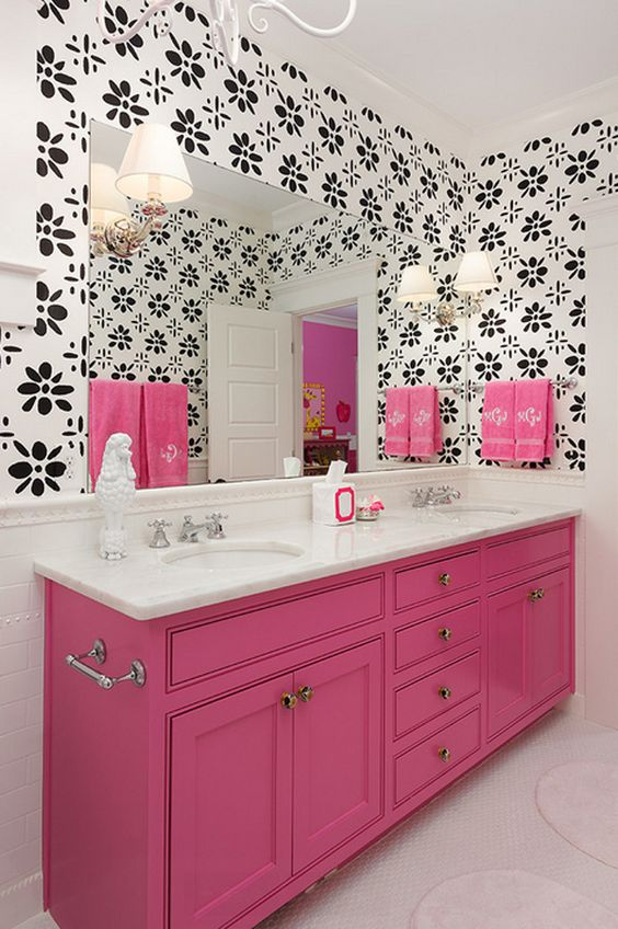 bathroom with white floor, shocking pink cabinet with white top, white sink, silver faucet, pink towels, white sconces, white black wallpaper