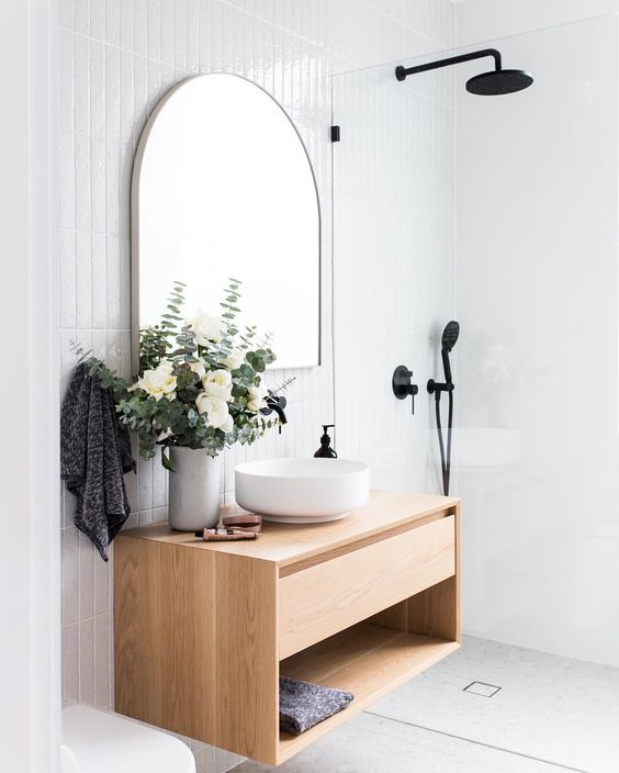 bathroom with white floor, white wall tiles, wooden floating vanity with small round sink, mirror