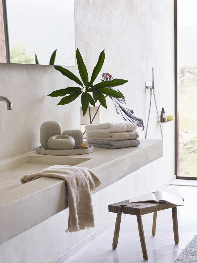 bathroom with white floor, white wall, white concrete sink vanity, plants, stool