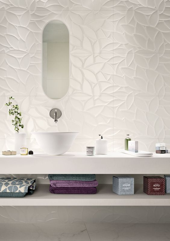 bathroom with white floor, white wooden shelves with white vanity top, white bowl sink, long vertical mirror, white textured wall