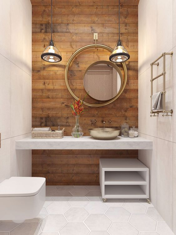 bathroom with white hexagonal tiles floor, smooth marble wall with wooden accent wall, white table with golden sink, white moving shelves, white toilet