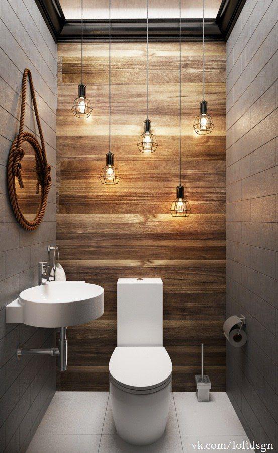 bathroom with white tile wall, wooden accent wall, white toilet, white sink, round mirror, lighting fixtures, white tiles
