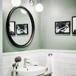 Bathroom With White Tiles On Half The Wall, Sage Green Painted On Half Top The Wall, Black Framed Round Mirror, White Sconces, Wooden Cabinet With Marble, White Sink