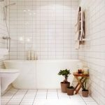 Bathroom With White Tiles On The Floor And Wall, White Tub, White Toilet, Shower, Wooden Stools, Rug, Plants