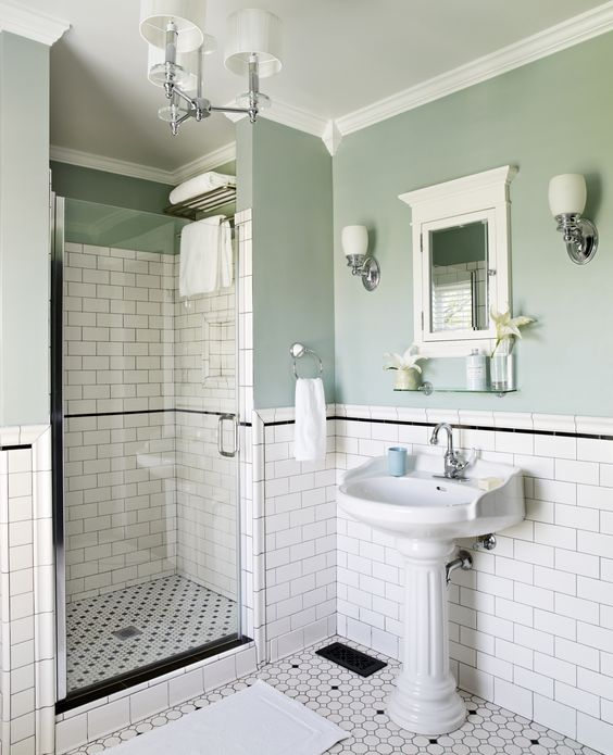 bathroom with white tiles on the floor differently, white subway tiles on the wall, sage green painted wall, white framed mirror, white sink, sconces,