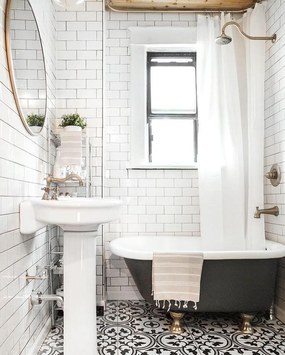 bathroom with white tiles on wall, patterned tiles on floor, white small vanity, round mirror, metal shelves